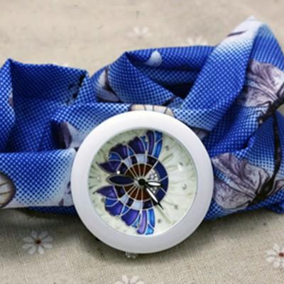 Orologio fiocco Farfalla Azzurra Orologio fiocco con una farfalla raffigurata sul quadrante e foulard con una decorazione di fiori su sfondo Azzurro